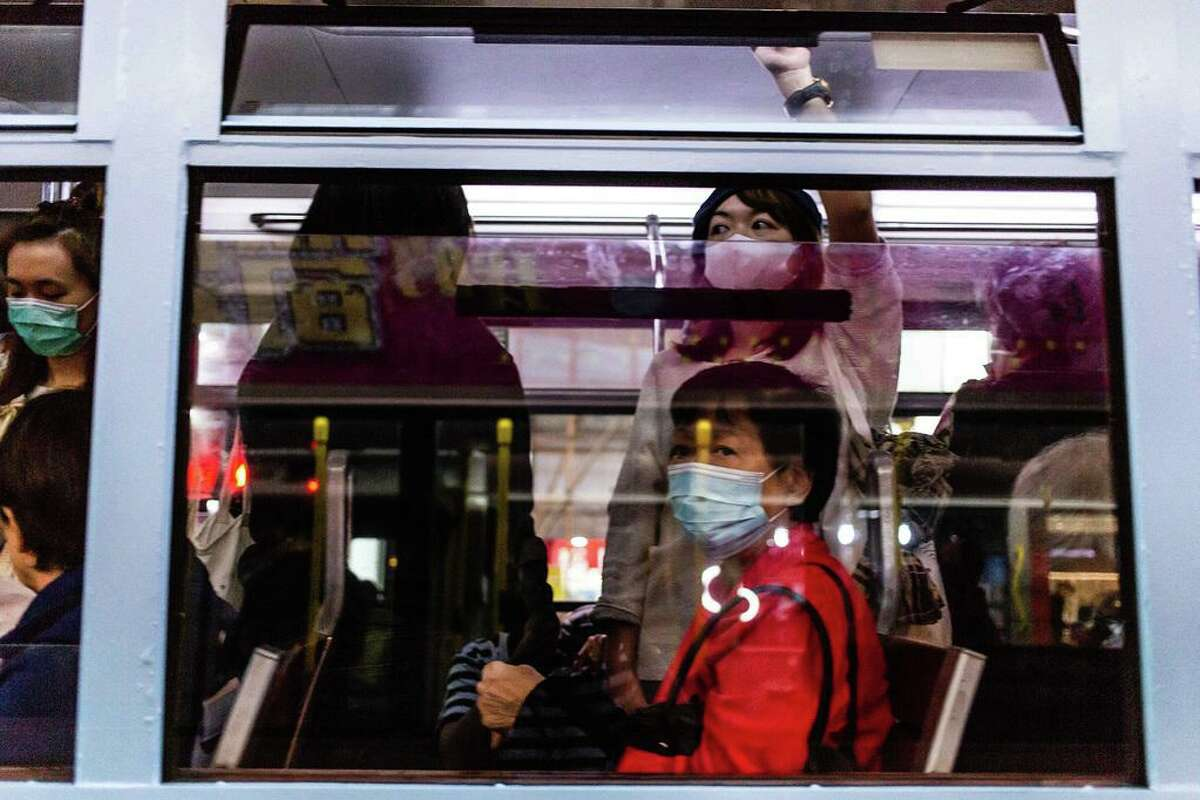 Passengers on a tram wear surgical masks on Friday in Hong Kong, China. A woman in Chicago who traveled to China earlier this month has been diagnosed with coronavirus.