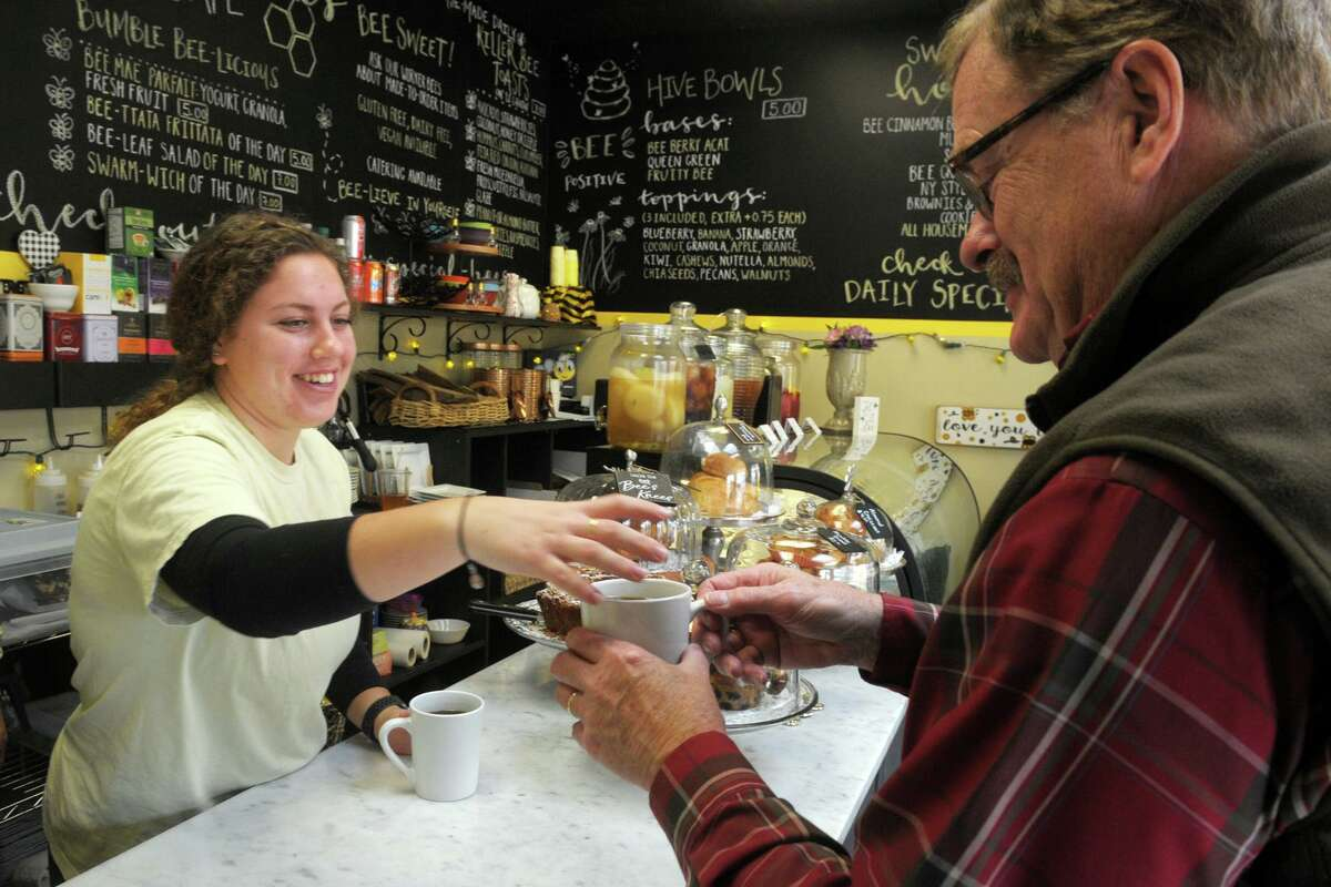 Mily Rowland serves a cup of coffee to customer at The Bee's Knees Cafe in the Walnut Beach neighborhood of Milford.