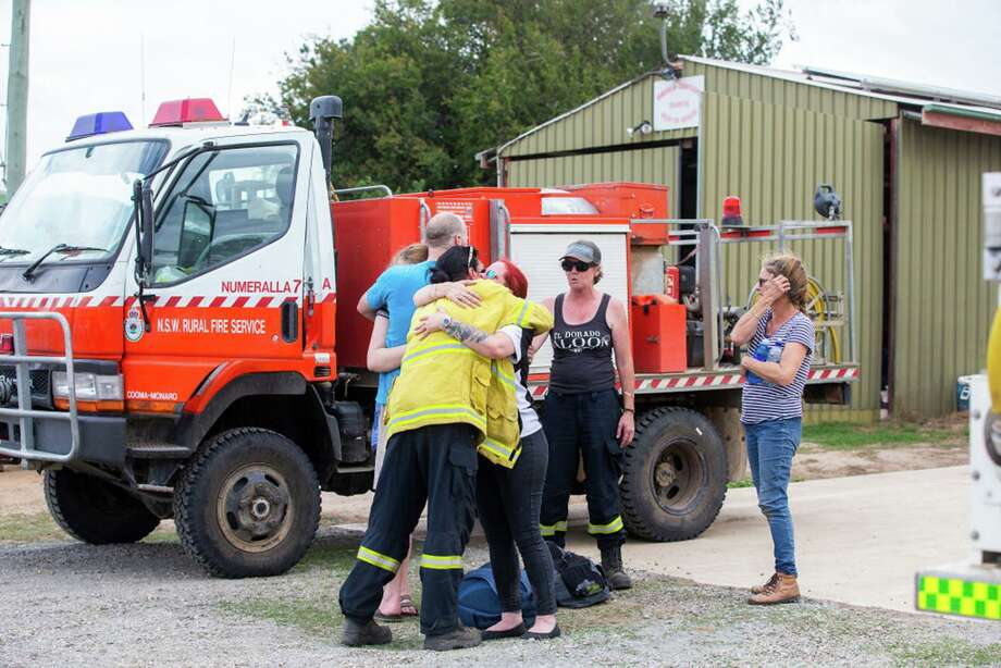People are seen embracing at Numeralla Rural Fire Brigade near the scene of a water tanker plane crash Thursday in Cooma, Australia. Three American firefighters died after their C-130 water tanker plane crashed while battling a bushfire near Cooma. Photo: Jenny Evans /Getty Images /TNS / Getty Images North America