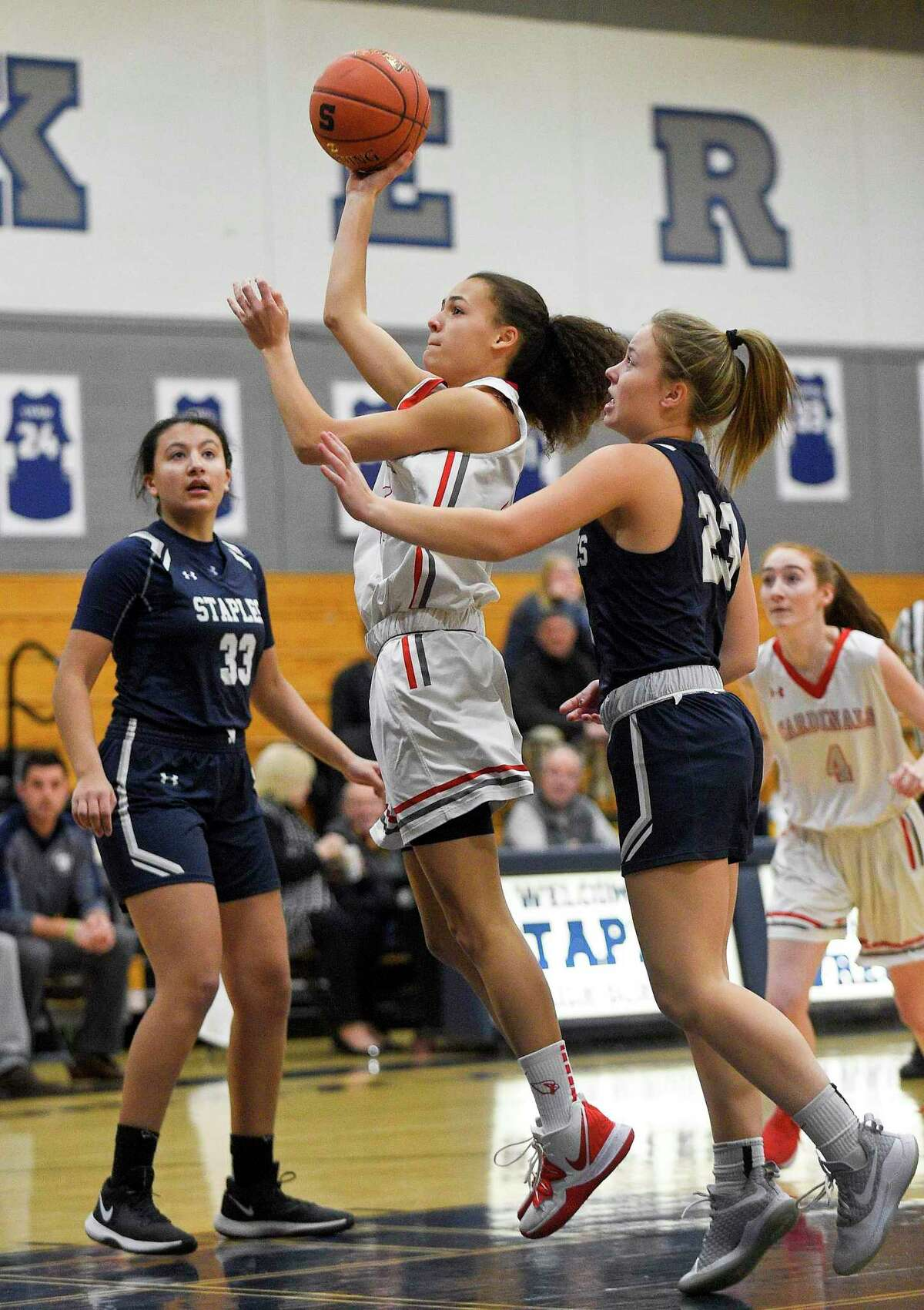 Greenwich's Makenzie Nelson (45) puts up a shot between Staples' Marley Lopez (33) and Abigail Cozzi (23) during a game in January.