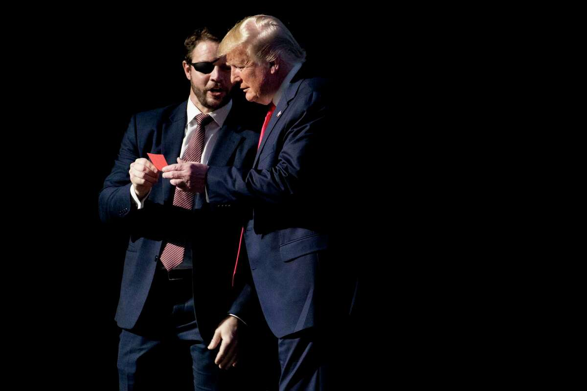 """U.S. Rep. Dan Crenshaw, R-Texas, left, comes on stage to hand President Donald Trump what he says is the """"No"""" vote card from Wednesday's House impeachment vote as Trump speaks at the Turning Point USA Student Action Summit at the Palm Beach County Convention Center in West Palm Beach, Fla., Saturday, Dec. 21, 2019."""
