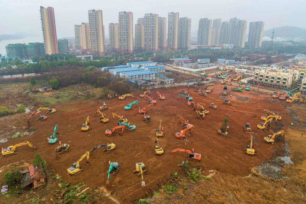 TOPSHOT - This aerial photo on January 24, 2020 shows excavators at the construction site of a new hospital being built to treat patients from a deadly virus outbreak in Wuhan in China's central Hubei province. - China is rushing to build a new hospital in a staggering 10 days to treat patients at the epicentre of a deadly virus outbreak that has stricken hundreds of people, state media reported on January 24. (Photo by STR / AFP) / China OUT (Photo by STR/AFP via Getty Images)