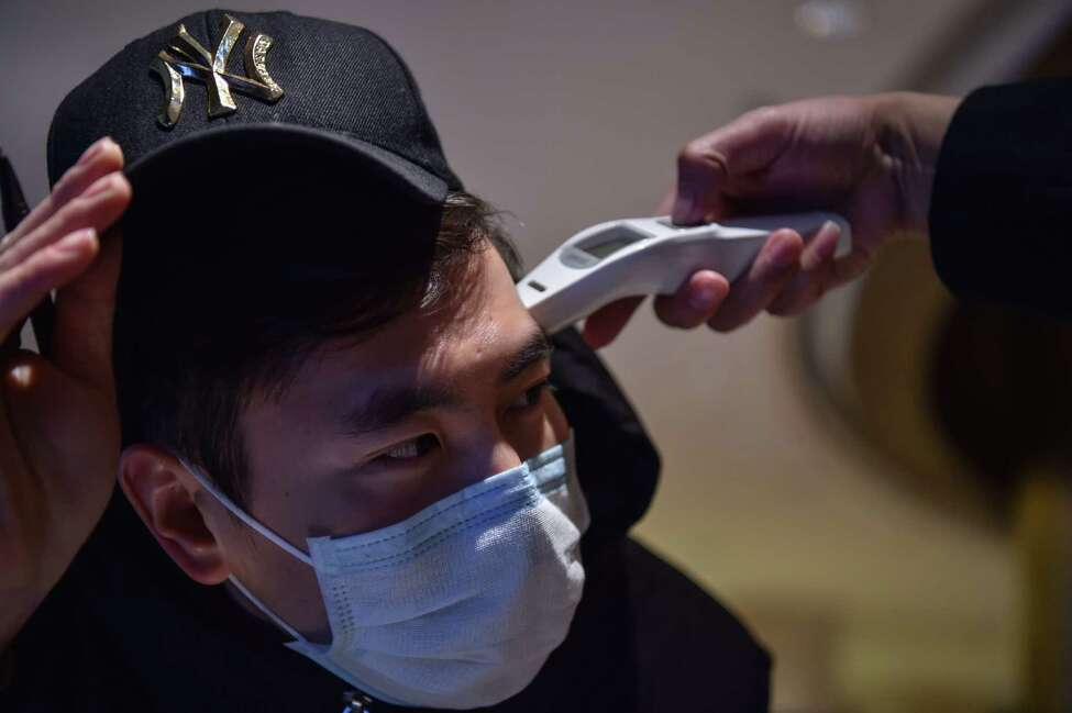 A hotel employee takes the temperature of a person that just arrived at the premise in Wuhan on January 24, 2020 - China placed the city at the centre of a virus outbreak under effective quarantine, suspending outward flights and trains in a drastic step to contain a contagious disease that has killed 17, stricken hundreds and reached other countries. (Photo by Hector RETAMAL / AFP) (Photo by HECTOR RETAMAL/AFP via Getty Images)