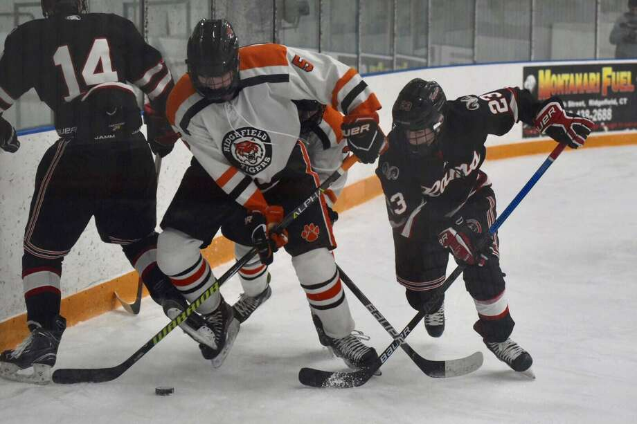 Ridgefield's Ryan Tullo and New Canaan's Boden Gammill (23) battle on the boards during the Rams' 2-0 victory on Friday at the Winter Garden in Ridgefield. Photo: David Stewart / Hearst Connecticut Media / Connecticut Post