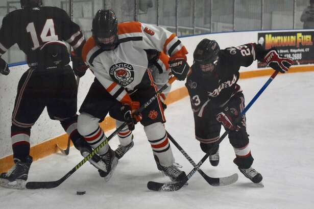 Ridgefield's Ryan Tullo and New Canaan's Boden Gammill (23) battle on the boards during the Rams' 2-0 victory on Friday at the Winter Garden in Ridgefield.