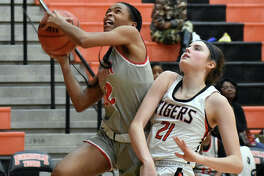 Alton guard Germayia Wallace goes up for a layup with Edwardsville forward Elle Evans trailing right behind her in the fourth quarter.