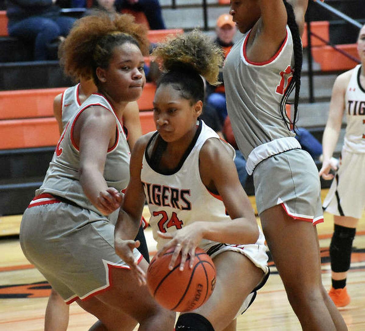 Edwardsville forward Ariana Bennett, center, fights through an Alton double team late in the fourth quarter on Friday inside Lucco-Jackson Gymnasium.