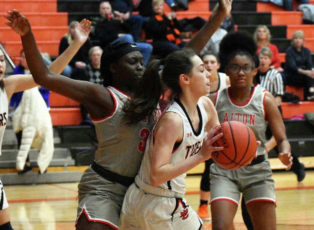 Edwardsville forward Emerson Weller looks to pass the ball out of the post with Alton's Lay'lhany Davis defending her late in the fourth quarter.