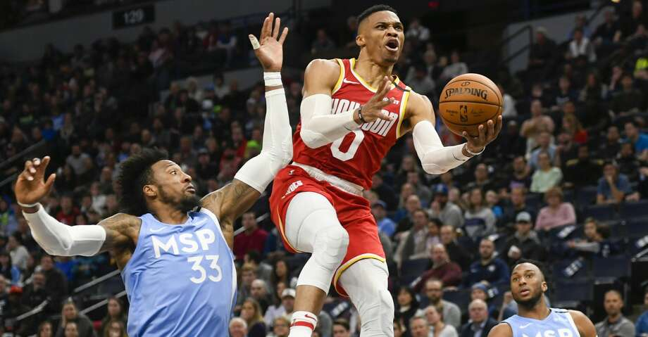 Houston Rockets guard Russell Westbrook (0) goes up for a layup past Minnesota Timberwolves forward Robert Covington (33) and guard Josh Okogie (20) during the second half of an NBA basketball game Friday, Jan. 24, 2020, in Minneapolis. (AP Photo/Craig Lassig) Photo: Craig Lassig/Associated Press