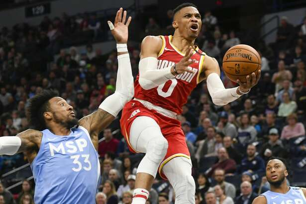 Houston Rockets guard Russell Westbrook(0) goes up for a layup past Minnesota Timberwolves forward Robert Covington(33) and guard Josh Okogie (20) during the second half of an NBA basketball game Friday, Jan. 24, 2020, in Minneapolis. (AP Photo/Craig Lassig)