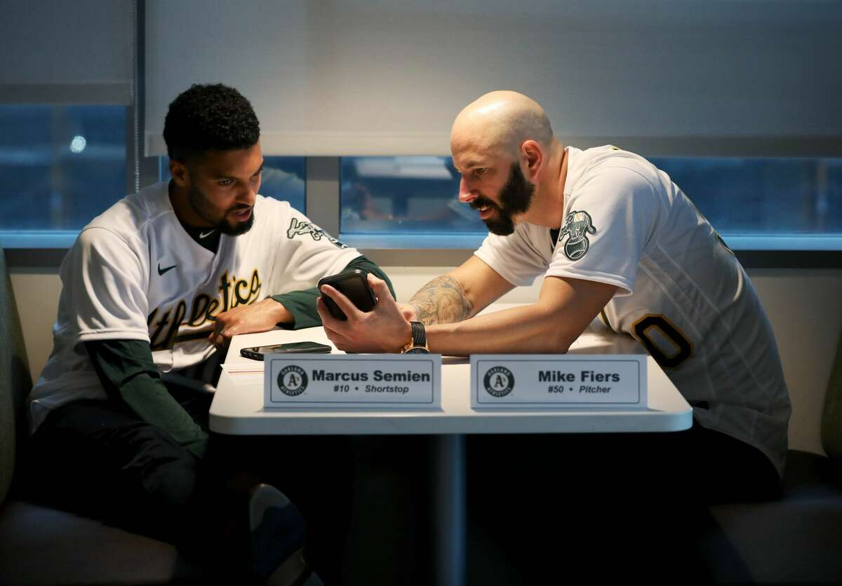 Marcus Semian, shortstop, left, and Mike Fiers, pitcher, converse during the Oakland A's pre-Fan Fest media availability at the A's offices at Jack London Square in Oakland, Calif., on Friday, January 24, 2020. Fiers is the only named whistleblower at the center of the Houston Astros' cheating scandal.