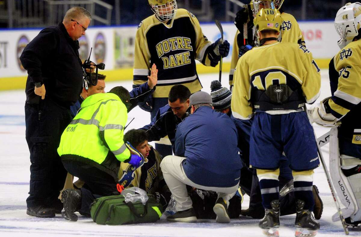Notre Dame of Fairfield's Mike Ceneri (17) is treated after being hit by Notre Dame of West Haven's John D'Errico during Connecticut Ice Tournament action at the Webster Bank Arena in Bridgeport, Conn., on Jan. 24, 2020. D'Errico was ejected from the game.