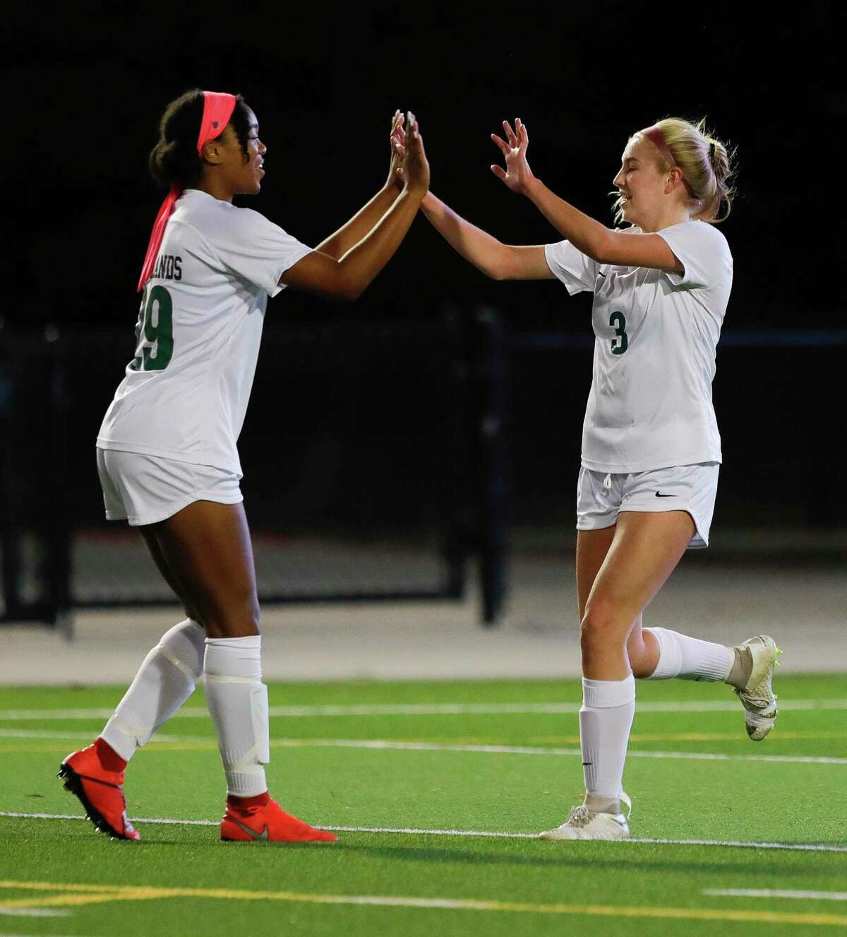 The Woodlands midfielder Courtney Koehler (3) gets a high-five from forward Samone Knight (29) after scoring a goal during the first period of a District 15-6A high school soccer match at Woodforest Bank Stadium, Friday, Jan. 24, 2020, in Shenandoah.