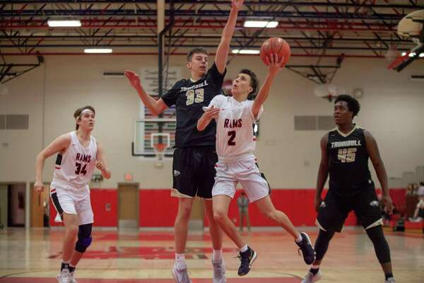 New Canaan's Aaron Fishman (2) drives against Trumbull's Andrew Cutter (33) during a boys basketball game on Friday, Jan. 24, 2020.
