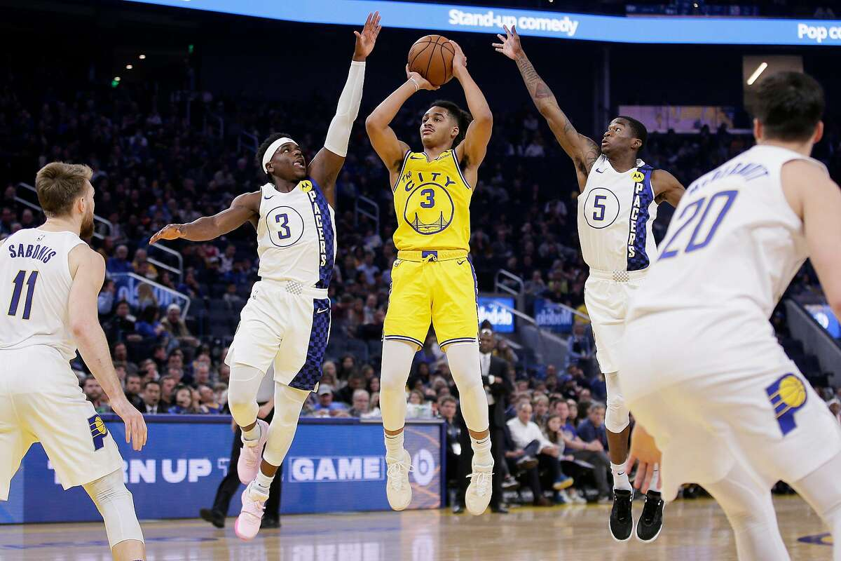 Golden State Warriors guard Jordan Poole (3) fakes a shot attempt and passes against Indiana Pacers guard Aaron Holiday (3) and Pacers guard Edmond Sumner (5) in the first half of an NBA game at Chase Center, Friday, Jan. 24, 2020, in San Francisco, Calif.
