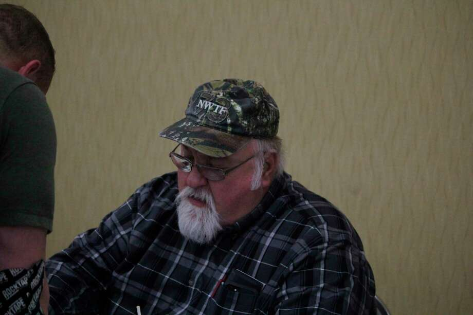 Former NWFT state director Tony Snyder works at his booth at the NWTF convention on Saturday. (Pioneer photo/John Raffel)