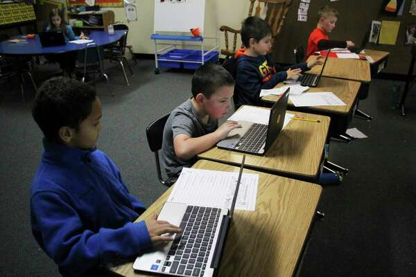 Tristian Patterson, Kaden Behnke and Jackson Checkley use Chromebooks to do classwork in Denise Gordon's second grade class. (Sara Eisinger/Huron Daily Tribune)