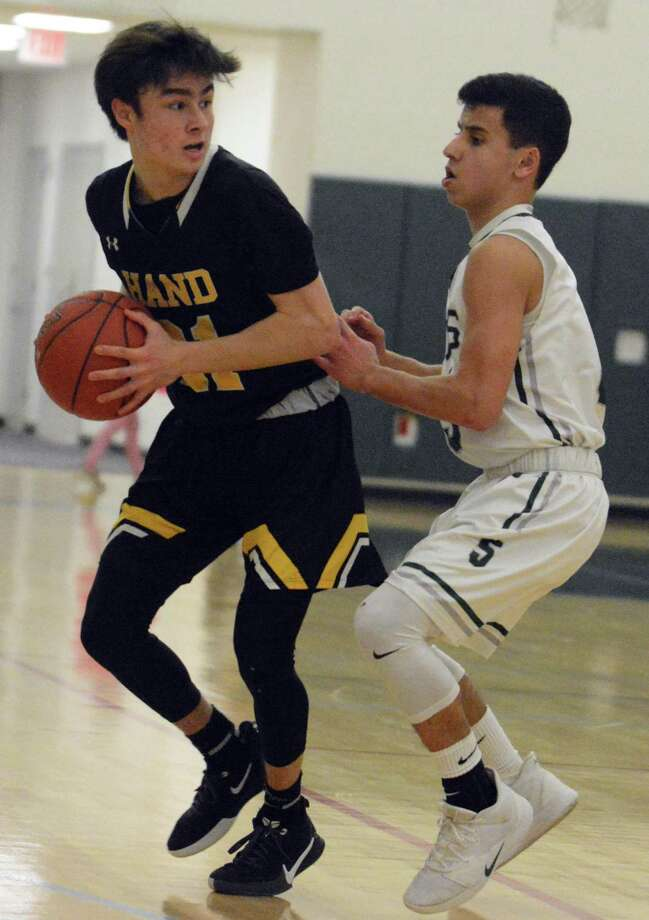 Hand's Ken Nuzzi is guarded by Guilford's Jake Ciocca Friday in an SCC boys basketball game. Photo: Dave Phillips / For Hearst Connecticut Media