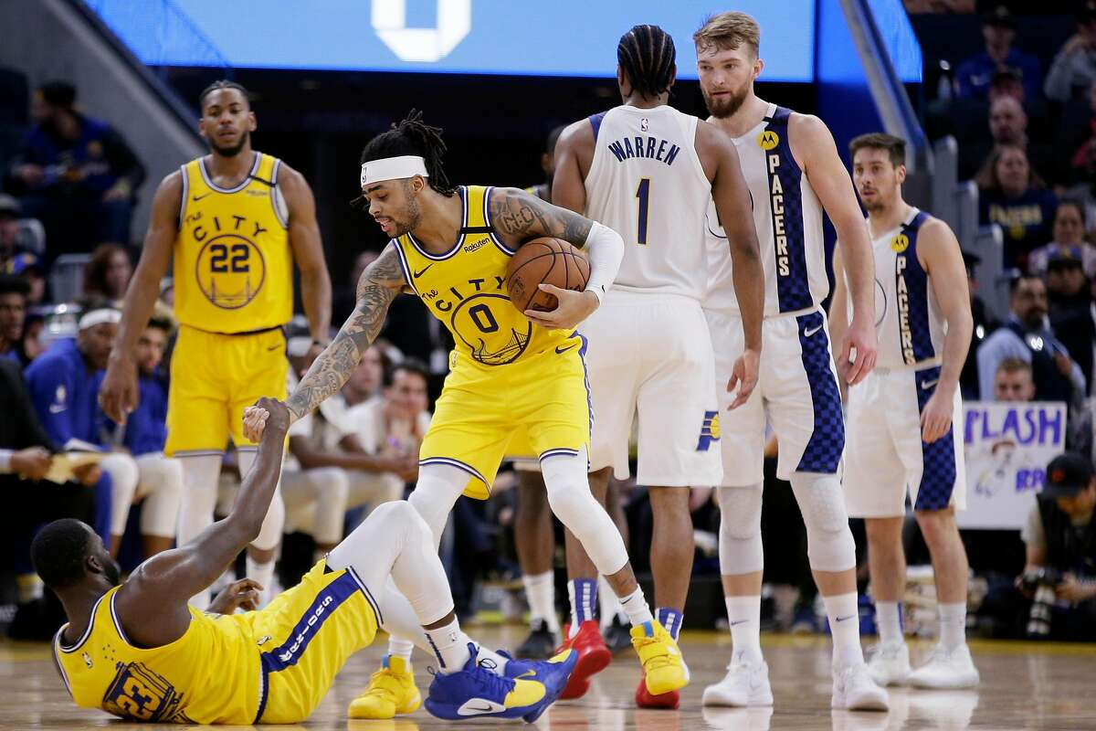 Golden State Warriors guard D'Angelo Russell (0) helps Warriors forward Draymond Green (23) up in the second half of an NBA game against the Indiana Pacers at Chase Center, Friday, Jan. 24, 2020, in San Francisco, Calif.