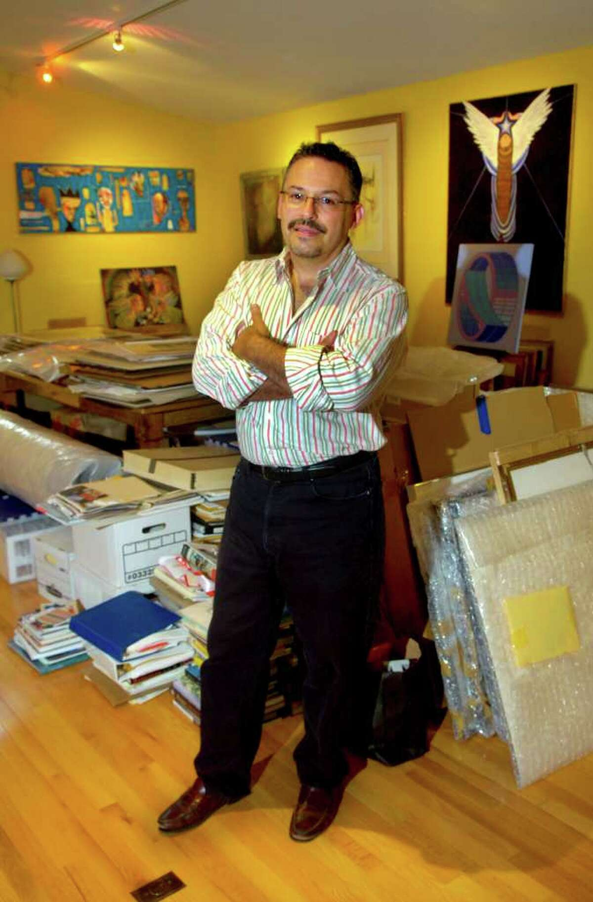 Ben Ortiz poses for a photo surrounded by his library of books and artwork stored in the studio on his property in Ridgefield. Ortiz is curating four art shows simultaneously in September.
