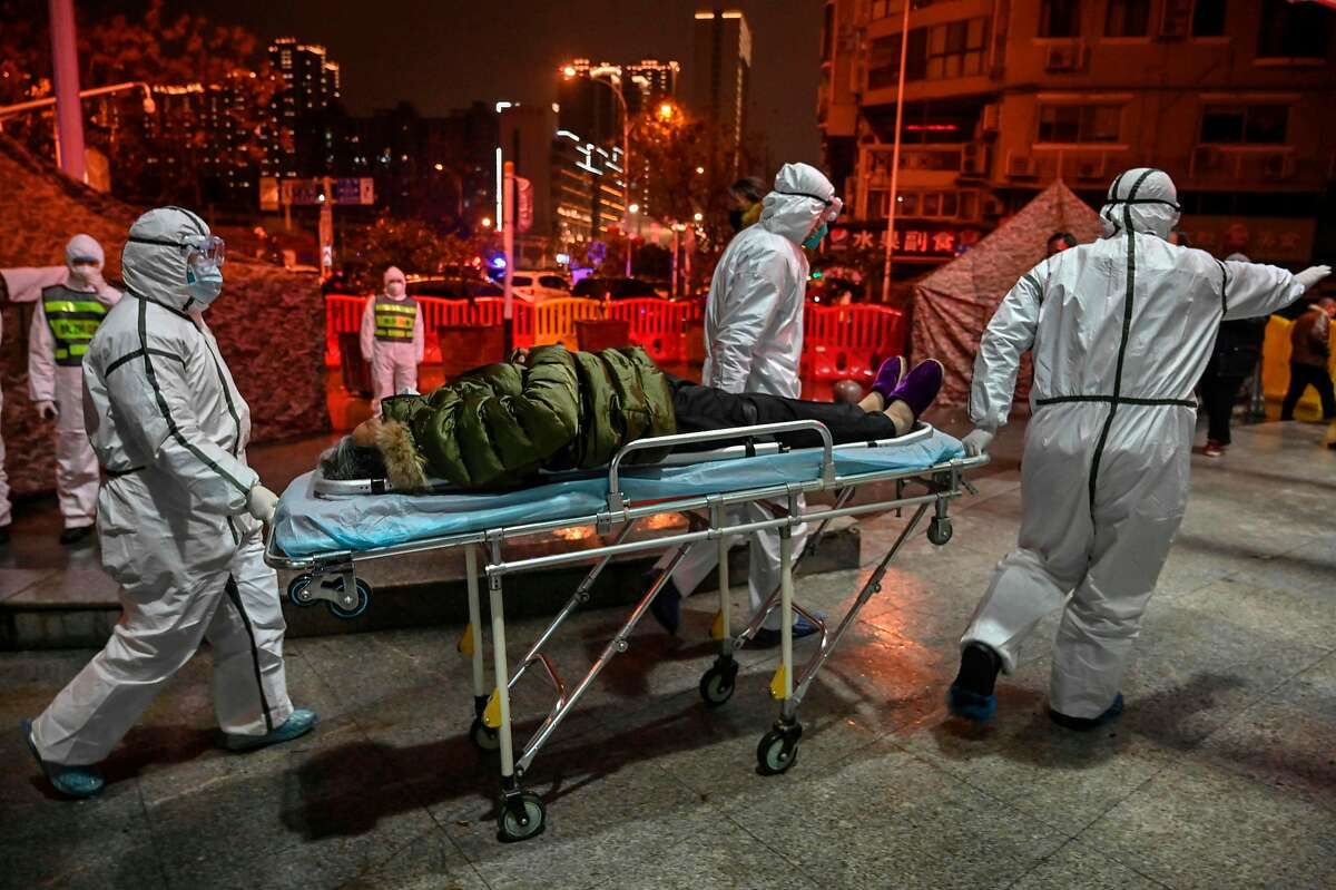 Medical staff members wearing protective clothing to help stop the spread of a deadly virus which began in the city, arrive with a patient at the Wuhan Red Cross Hospital in Wuhan on January 25, 2020. - The Chinese army deployed medical specialists on January 25 to the epicentre of a spiralling viral outbreak that has killed 41 people and spread around the world, as millions spent their normally festive Lunar New Year holiday under lockdown. (Photo by Hector RETAMAL / AFP) (Photo by HECTOR RETAMAL/AFP via Getty Images)