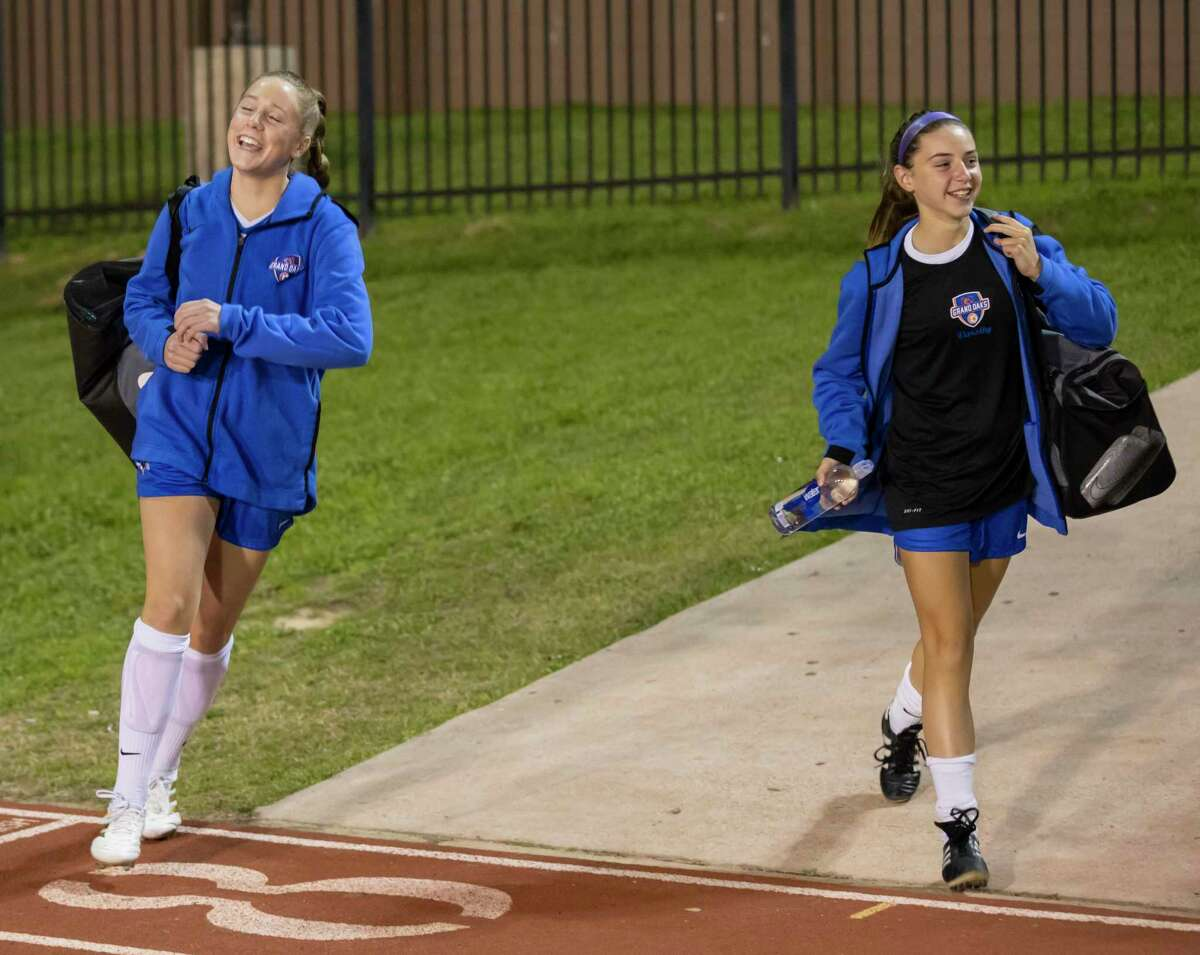 Lauren Moylan, right, and Reese Rupe, left, walk into Berton A. Yates Stadium for a District 20-5A high school soccer match. Moylan and Rupe are two of four Grand Oaks students who play both junior varsity basketball and varsity soccer.