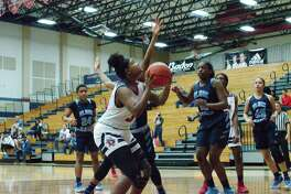 Dawson's Braelyn Younger (34) tries to put up a shot over Alief Elsik's Maia English Friday at Dawson High School.