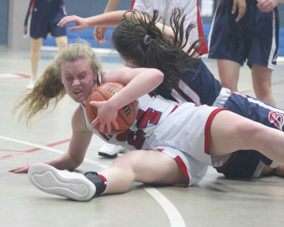 Pasadena-First Baptist Christian Academy's Jenna Patteson protects the basketball as she and a Lady Bronco hit the floor. Players hitting the floor proved to be a common sight in Friday night's game. Photo: Robert Avery