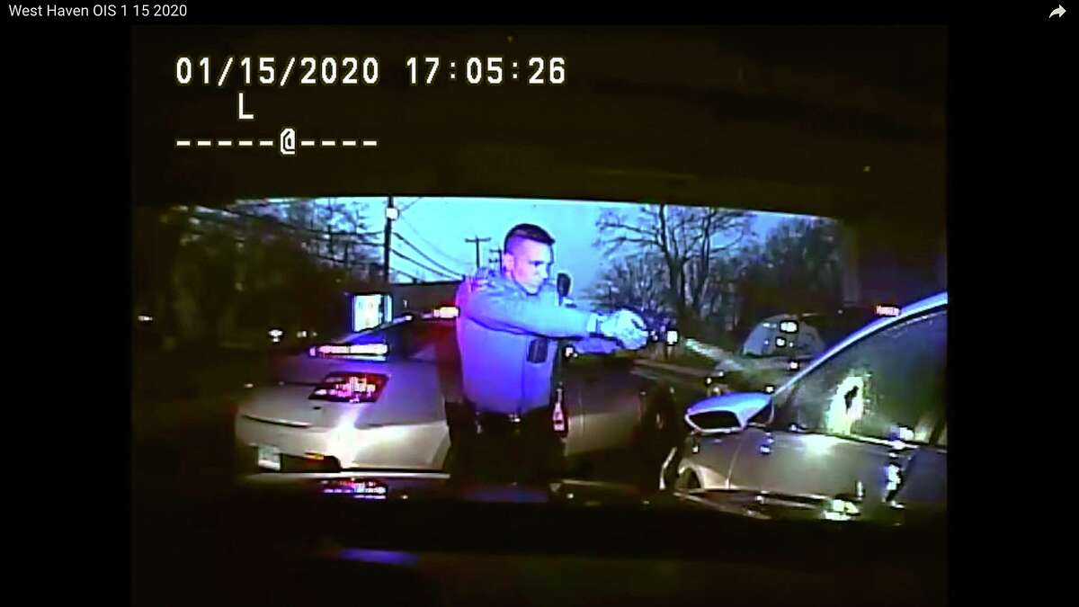 This Jan. 15, 2020, still image from dashboard camera video released by the Connecticut State Police shows Trooper Brian North, left, after he discharged his weapon beside vehicle stopped in West Haven, Conn. North fatally shot Mubarak Soulemane following a high-speed chase along Interstate 95 after Soulemane,19, had carjacked the vehicle in Norwalk, Conn. Clergy and relatives of Soulemane have called for the trooper be sent home on suspension and are asking for more de-escalation training. (Connecticut State Police via AP)