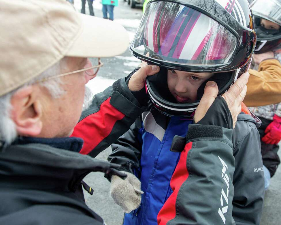 Dom Jacangelo, executive director of the New York State Snowmobile Association, makes sure a helmet fits on Carter Hansen, of Niskayuna, during the Grafton Lakes' 35th Annual Winter Fest on Saturday, Jan. 25, 2019 (Jim Franco/Special to the Times Union.)