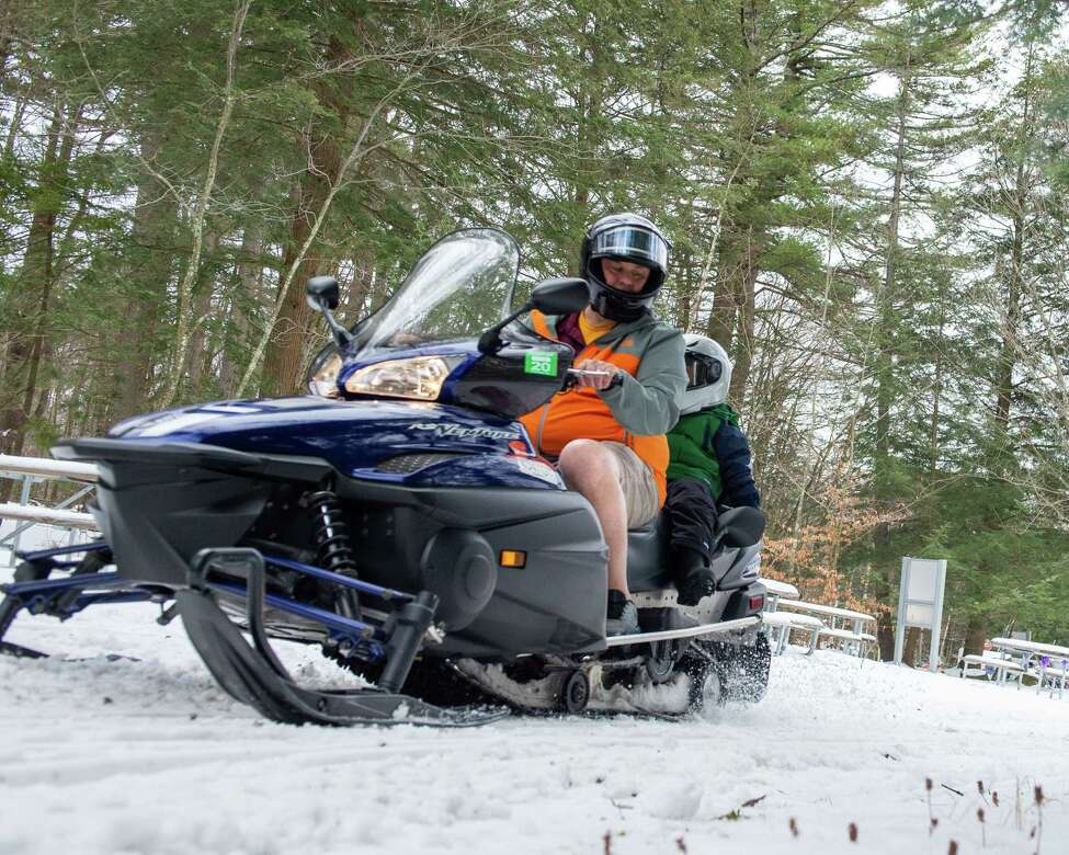 Scott Rice, of Schaghticoke, wears shorts while taking his son, Joseph Rice, on a snowmobile ride during the Grafton Lakes' 35th Annual Winter Fest on Saturday, Jan. 25, 2019 (Jim Franco/Special to the Times Union.)