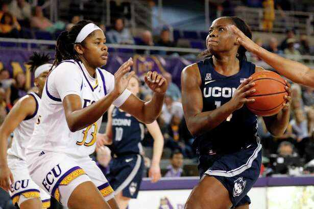 UConn's Evelyn Adebayo, right, drives the ball against East Carolina's Tiara Chambers during the second half on Saturday.