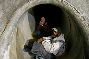 Phillip Kenowitz (left rear), and Marv Mitchel talk about being homeless while trying to stay warm in a drainage tunnel at I-10W and De Zavala Road Thursday Jan. 11, 2018.