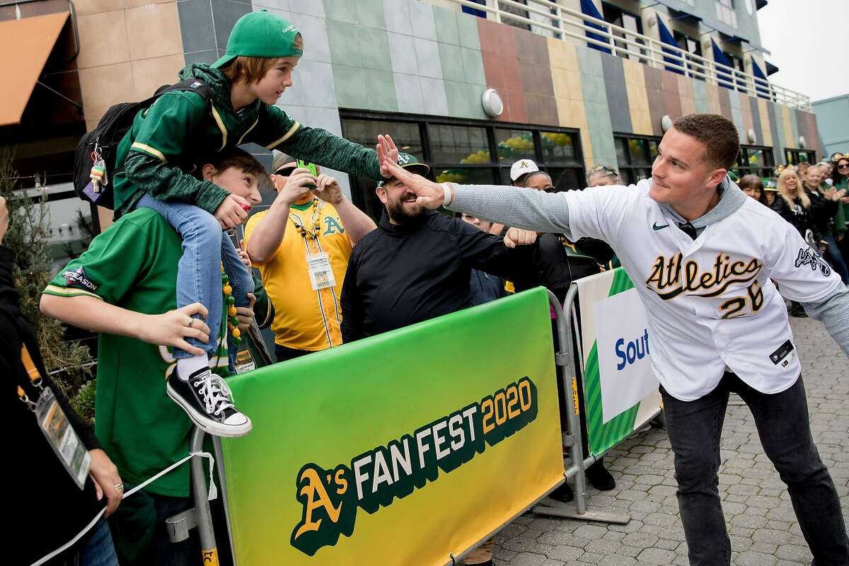 Oakland A's third baseman Matt Chapman high-fives a fan in the crowds during the player's procession kicking off the Oakland A's Fan Fest held at Jack London Square in Oakland, Calif. Saturday, January 25, 2020.