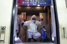 A worker in protective gear in Seoul, South Korea, sprays disinfectant in a train on Jan. 24 amid rising public concerns over the spread of China's Wuhan coronavirus, which medical experts have confirmed can be passed from human to human.