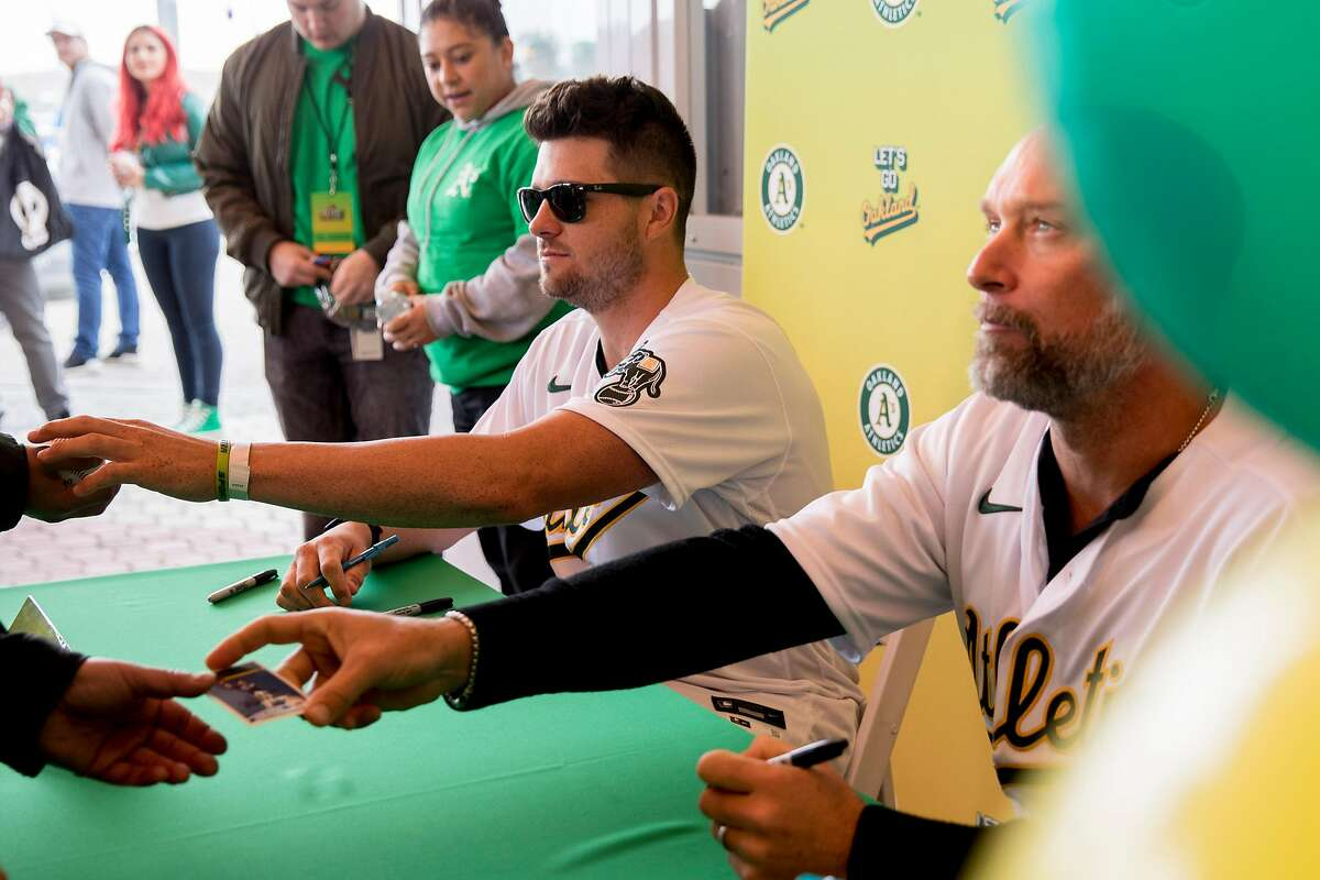 Oakland A's catcher Austin Allen (left) and former Oakland A's outfielder Mark Kotsay sign autographs for fans during the Oakland A's Fan Fest held at Jack London Square in Oakland, Calif. Saturday, January 25, 2020.