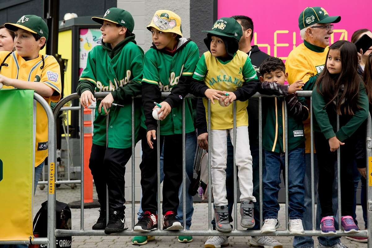 Young A's fans climb onto the barricades along the parade route to get a peek at their favorite players during the player's procession kicking off the Oakland A's Fan Fest held at Jack London Square in Oakland, Calif. Saturday, January 25, 2020.