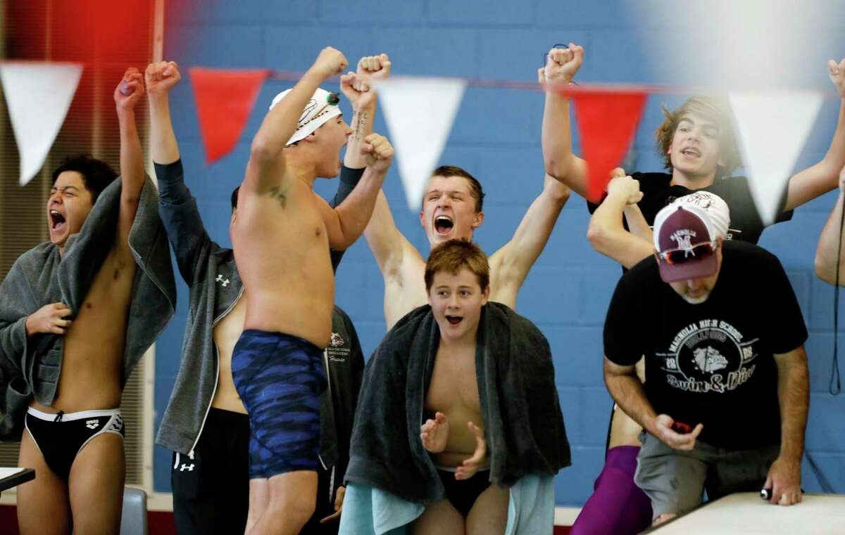 Magnolia swimmers cheer as they compete in the boys 200-yard freestyle relay during the District 21-5A swimming championships at the Tomball ISD Aquatic Center, Saturday, Jan. 25, 2020, in Tomball.