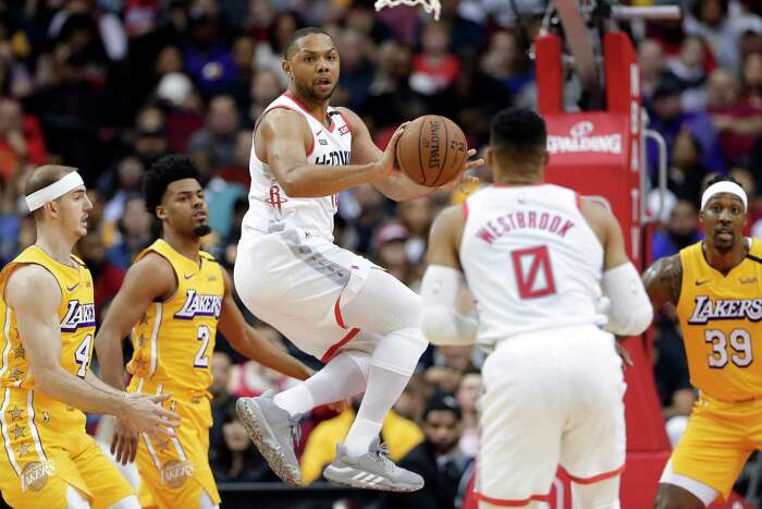 Houston Rockets guard Eric Gordon, middle, passes the ball to guard Russell Westbrook (0) in front of Los Angeles Lakers guard Alex Caruso (4), guard Quinn Cook (2) and center Dwight Howard (39) during the first half of an NBA basketball game Saturday, Jan. 18, 2020, in Houston. (AP Photo/Michael Wyke)
