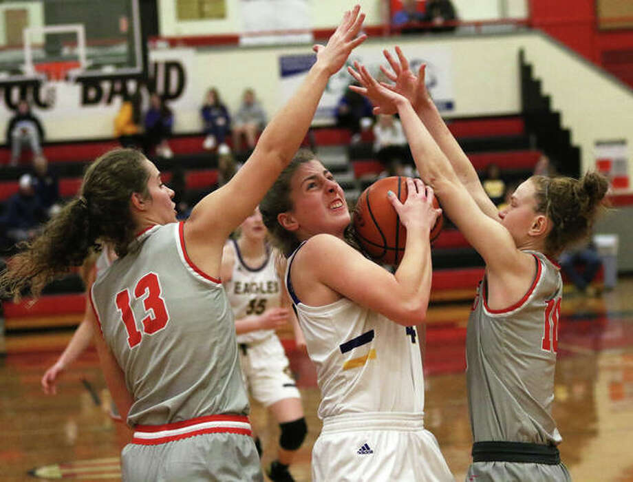 CM's Jackie Woelfel splits Highland defenders Bella LaPorta (13) and Kirsten Taylor (right) in the lane and scores in the first half Saturday at the 34th annual Scott Credit Union Tournament in Highland. Photo: Greg Shashack / The Telegraph