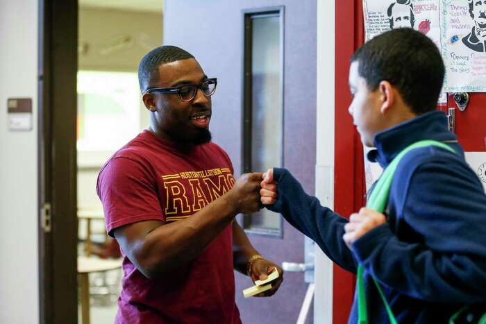 Holub Middle School eighth-grade language arts teacher Maurice Daniels-Fleming greets one of his students in the hallway at Holub Middle School in Houston on Friday.