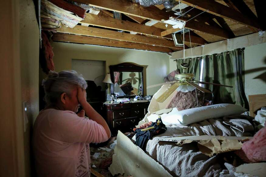 Marycruz Hernandez covers her face as she picks up a phone call inside her bedroom Saturday, Jan. 25, 2020, in Houston. Hernandez said her get out from under fallen sheetrock following the explosion at Watson Grinding and Manufacturing.