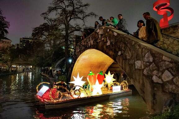 People watch a decorated float traveling along the San Antonio River during the Ford Parade of Lanterns. The illuminated spectacle will occur nightly through Feb. 8.