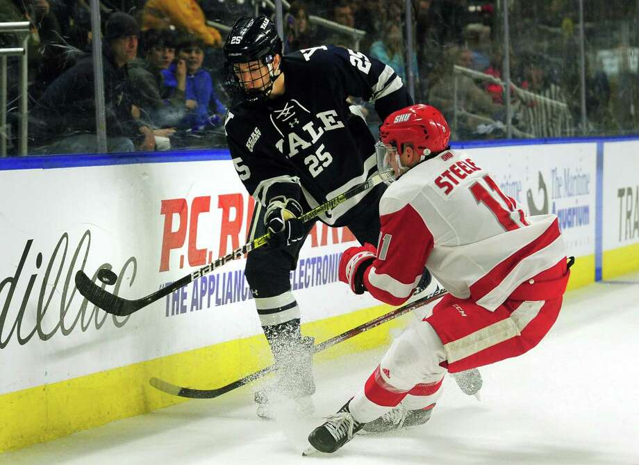 Yale's Phil Kemp passes the puck as Sacred Heart University's Ryan Steele converges during the Connecticut Ice Tournament at the Webster Bank Arena in Bridgeport in January. Yale has paused workouts after positive tests by members of the men's hockey program. Photo: Christian Abraham / Hearst Connecticut Media / Connecticut Post