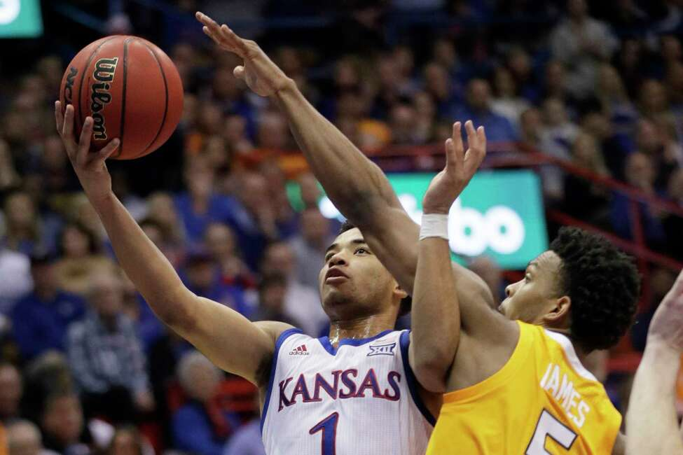 Kansas guard Devon Dotson (1) gets past Tennessee guard Josiah-Jordan James (5) for a basket during the first half of an NCAA college basketball game in Lawrence, Kan., Saturday, Jan. 25, 2020. (AP Photo/Orlin Wagner)