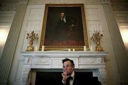 Fritz Klein, an actor playing the role of former President Abraham Lincoln, sits in character beneath the 16th president's portrait in the State Dining Room at the White House.