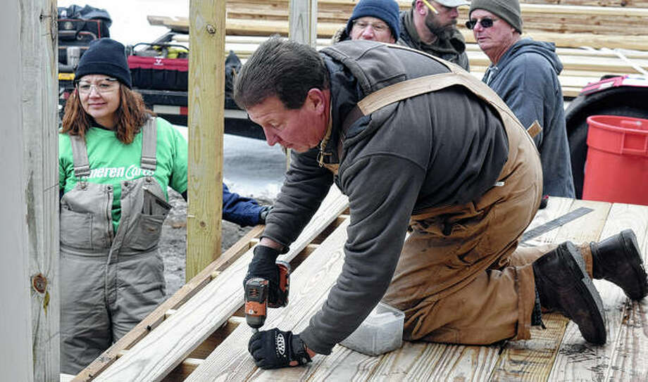 Chris Wilcox of Waverly drills wood into place to set up a ramp for former firefighter Jim Watts on Saturday. Watts' friends joined to help him after he was left paralyzed by a fall in November. Photo: Marco Cartolano| Journal-Courier
