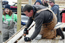 Chris Wilcox of Waverly drills wood into place to set up a ramp for former firefighter Jim Watts on Saturday. Watts' friends joined to help him after he was left paralyzed by a fall in November.