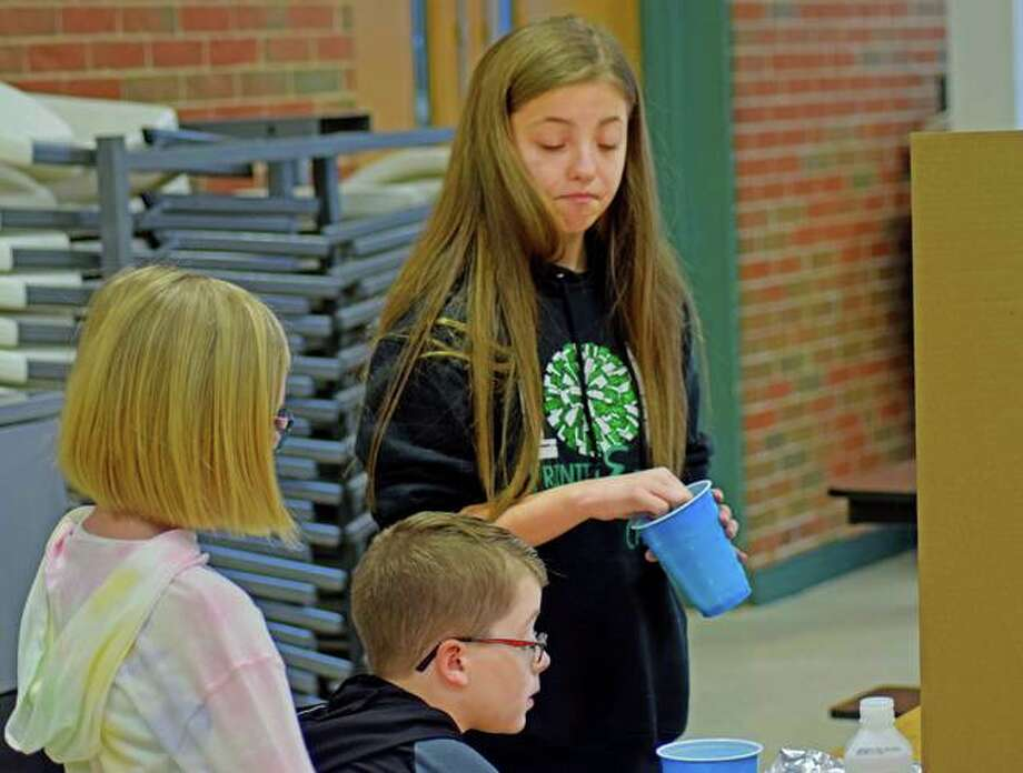 Annika Jenkins, a fifth-grader at Trinity Lutheran, makes a facial expression as she lets a second-grader take part in her science demonstration Friday morning. Photo: Tyler Pletsch | The Intelligencer
