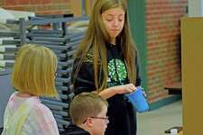 Annika Jenkins, a fifth-grader at Trinity Lutheran, makes a facial expression as she lets a second-grader take part in her science demonstration Friday morning.